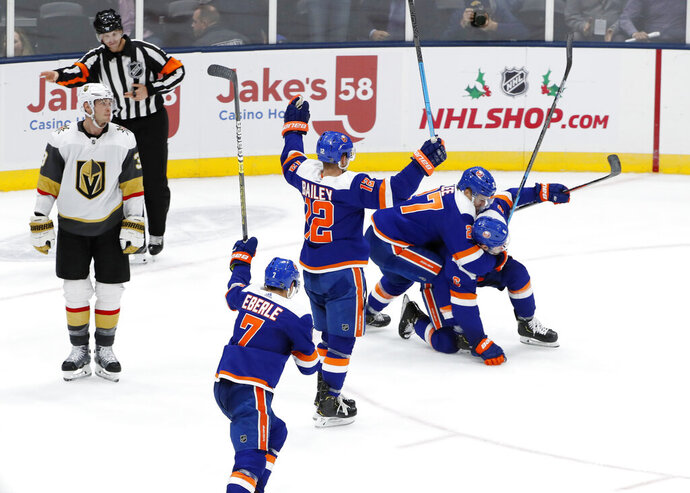 New York Islanders left wing Anders Lee (27) tackles defenseman Ryan Pulock (6), who scored in overtime of an NHL hockey game against the Vegas Golden Knights, Thursday, Dec. 5, 2019, in Uniondale, N.Y. Islanders right wings Jordan Eberle (7) and Josh Bailey (12) celebrate with raised sticks. (AP Photo/Kathy Willens)