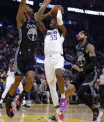 Dallas Mavericks' Delon Wright, center, shoots between Golden State Warriors' Alec Burks, left, and Willie Cauley-Stein (2) in the first half of an NBA basketball game Tuesday, Jan. 14, 2020, in San Francisco. (AP Photo/Ben Margot)