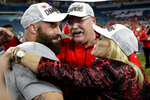 CORRECTS ID AT LEFT TO ANTHONY SHERMAN, NOT TRAVIS KELCE - Kansas City Chiefs head coach Andy Reid, center, celebrates with wife Tammy, right, and Anthony Sherman after the NFL Super Bowl 54 football game against the San Francisco 49ers, Sunday, Feb. 2, 2020, in Miami Gardens, Fla. The Kansas City Chiefs won 31-20. (AP Photo/Patrick Semansky)