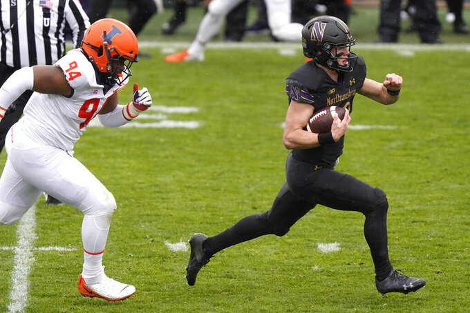 Northwestern quarterback Peyton Ramsey, right, runs with the ball past Illinois defensive line Jer'Zhan Newton during the first half of an NCAA college basketball game in Evanston, Ill., Saturday, Dec. 12, 2020. (AP Photo/Nam Y. Huh)