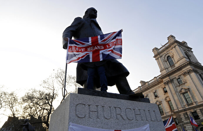 FILE - In this file photo dated Friday, March 29, 2019, a pro-Brexit demonstrator holds a British flag with the words