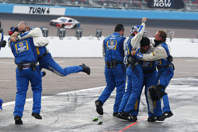 Chase Elliott's pit crew celebrates in their pit stall after winning the season championship and the NASCAR Cup Series auto race at Phoenix Raceway, Sunday, Nov. 8, 2020, in Avondale, Ariz. (AP Photo/Ralph Freso)