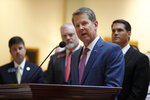 Georgia Gov. Brian Kemp, center, joined by medical marijuana users and advocates, speaks at a news conference where his signed HB 324, Wednesday, April 17, 2019, in Atlanta. The legislation allows the in-state production and sale of the marijuana oil and closes a loophole in a 2015 law that banned growing, buying and selling the drug but allowed certain patients to possess it. (Bob Andres/Atlanta Journal-Constitution via AP)
