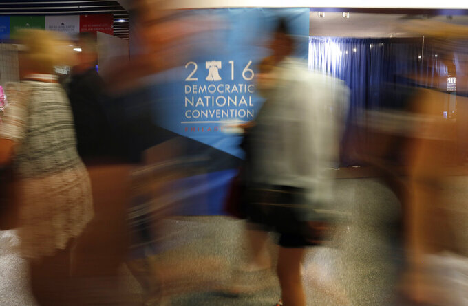 FILE - In this July 28, 2016, file photo attendees walk a hall in the Wells Fargo Center before the start of the final day of the Democratic National Convention in Philadelphia. The coronavirus pandemic is forcing Democrats and Republicans to take a close look at whether they'll be able to move forward as planned this summer with conventions that typically kick off the general election season. (AP Photo/Paul Sancya, File)
