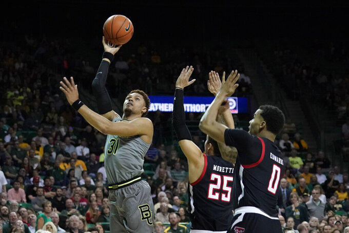 Baylor's MaCio Teague (31) drives past Texas Tech's Davide Moretti (25) and Kyler Edwards (0) during the first half of an NCAA college basketball game in Waco, Texas, Monday, March 2, 2020. (AP Photo/Chuck Burton)