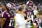 Texas A&M wide receiver Ainias Smith (17), coach Jimbo Fisher and quarterback Kellen Mond (11) celebrate after the team's 24-21 win against Oklahoma State in the Texas Bowl NCAA college football game Friday, Dec. 27, 2019, in Houston. (AP Photo/Michael Wyke)