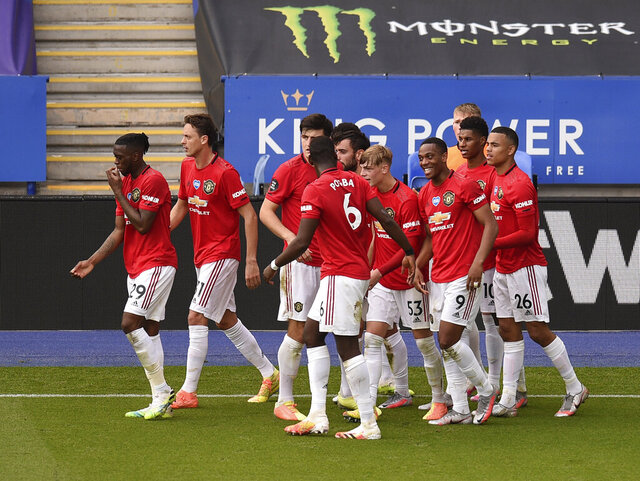Manchester United's Bruno Fernandes celebrates with teammates after scoring his side's opening goal from the penalty spot during the English Premier League soccer match between Leicester City and Manchester United at the King Power Stadium, in Leicester, England, Sunday, July 26, 2020. (Oli Scarff/Pool via AP)