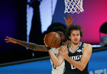 Sacramento Kings' Nemanja Bjelica, right, handles the ball against the New Orleans Pelicans during the first half of an NBA basketball game Tuesday, Aug. 11, 2020, in Lake Buena Vista, Fla. (Mike Ehrmann/Pool Photo via AP)