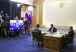 Russian President Vladimir Putin, right, Deputy Prime Minister of Russia Dmitry Kozak, second right, and Russian Minister of Energy Alexander Novak, back to a camera attend a joint video conference with Chinese President Xi Jinping during inaugurating the Power of Siberia pipeline in the Bocharov Ruchei residence in the Black Sea resort of Sochi, Russia, Monday, Dec. 2, 2019. China and Russia launched Monday a more than 6,000 kilometer-long gas pipeline in one realization of the countries' long-planned energy partnerships. (Mikhail Klimentyev, Sputnik, Kremlin Pool Photo via AP)