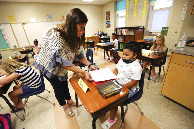 Corinth Elementary School third grade teacher Brooke Marlar helps her new student Navaeh Malone, get started with her assignment on the first day back to school on Monday, July 27, 2020 in Corinth, Miss. (Adam Robison/The Northeast Mississippi Daily Journal via AP)