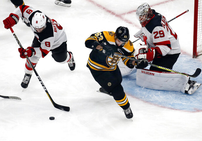 New Jersey Devils defenseman Will Butcher (8) clears the puck away from Boston Bruins left wing Brad Marchand (63) as Devils goaltender Mackenzie Blackwood (29) minds the net during the first period of an NHL hockey game Thursday, Dec. 27, 2018, in Boston. (AP Photo/Elise Amendola)