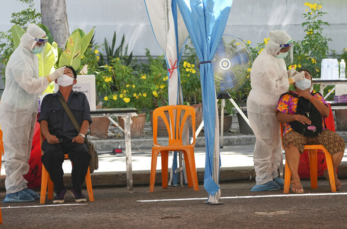 Health workers collect nasal swabs from local residents for coronavirus testing in Bangkok, Thailand, Tuesday, June 1, 2021. (AP Photo/Sakchai Lalit)