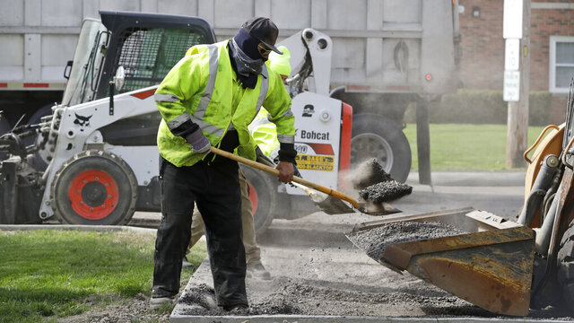 FILE - In this May 6, 2020 file photo, Jarrett Barth, who works for Dagg's Asphalt & Sealcoating, shovels gravel into a backhoe bucket in Lyndhurst, Ohio. U.S. productivity fell a sharp 2.5% in the first three months of this year as labor costs jumped 4.8%. The Labor Department reported that the decline in productivity, the amount of output per hour of work, followed a 1.2% gain in the fourth quarter of last year.(AP Photo/Tony Dejak)