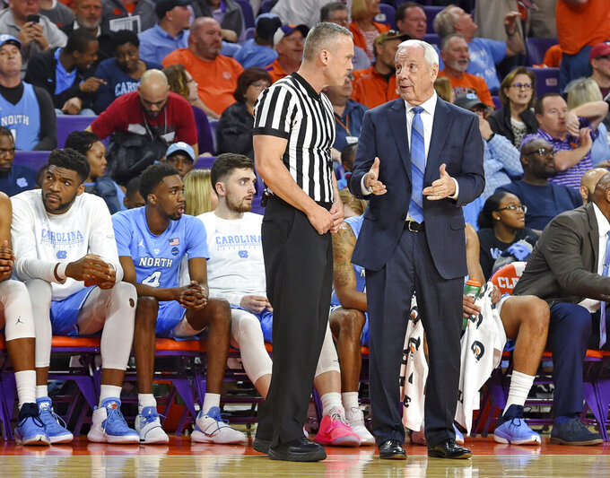 UNC's Roy Williams falls near bench, helped off court
