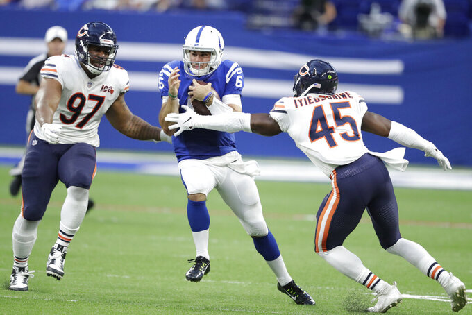Indianapolis Colts quarterback Chad Kelly (6) runs between Chicago Bears defensive tackle Nick Williams (97) and Joel Iyiegbuniwe (45) during the first half of an NFL preseason football game, Saturday, Aug. 24, 2019, in Indianapolis. (AP Photo/Michael Conroy)