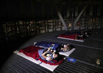 People wearing face masks to help protect against the spread of the coronavirus, stay at an overnight camping site on the roof of a skyscraper in Seoul, South Korea, Friday, Aug. 7, 2020. The Lotte World Tower, a 555-meter high skyscraper with 123 floors, opened social distancing camping areas on the tower's roof and ground for people who are tired in the hot summer weather and from COVID-19, as a part of a promotional event. (AP Photo/Lee Jin-man)