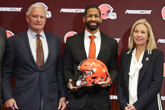 FILE - In this Feb. 5, 2020, file photo, Cleveland Browns general manager Andrew Berry, center, poses for a photo with owners Jimmy Haslam, left, and Dee Haslam, right, after speaking during a news conference at the NFL football team's training facility in Berea, Ohio. The Cleveland Browns have hired former 49ers executive Kwesi Adofo-Mensah as their new vice president of football operations under first-year general manager Andrew Berry. (AP Photo/Tony Dejak, File)