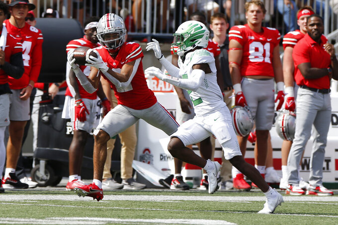 Ohio State receiver Chris Olave, left, catches a pass in front of Oregon defensive back Mykael Wright during the second half of an NCAA college football game Saturday, Sept. 11, 2021, in Columbus, Ohio. Oregon beat Ohio State 35-28. (AP Photo/Jay LaPrete)