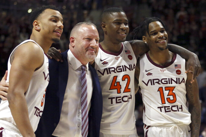 Virginia Tech coach Buzz Williams poses for a photograph with seniors Justin Robinson, Ty Outlaw (42) and Ahmed Hill (13) before the team's NCAA college basketball game against Miami in Blacksburg, Va., Friday, March 8, 2019. (Matt Gentry/The Roanoke Times via AP)