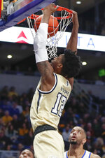 Pittsburgh's Abdoul Karim Coulibaly (12) dunks over Pittsburgh's Terrell Brown during the first half of an NCAA college basketball game, Saturday, Feb. 8, 2020, in Pittsburgh. (AP Photo/Keith Srakocic)