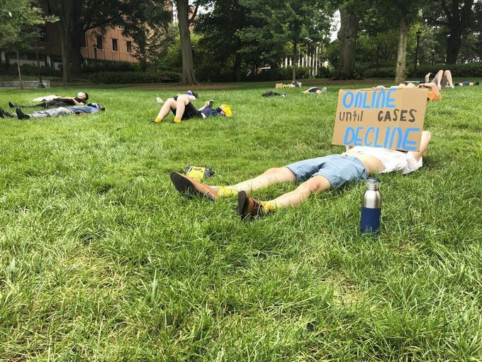 """A protester holds a sign opposing in-person classes Monday, August 17, 2020, at a """"die-in"""" at Georgia Tech in Atlanta. More of the state's public universities are opening for the fall term, trying to balance concern about COVID-19 infections against a mandate for on-campus classes citing financial needs and student desires (AP Photo/Jeff Amy)"""