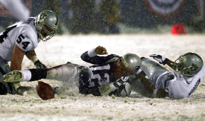 FILE - In this Jan. 19, 2002, file photo, New England Patriots quarterback Tom Brady (12) loses the ball after being brought down by Oakland Raiders' Charles Woodson, right, while Raiders' Greg Biekert (54) moves to recover the ball in the fourth quarter of their AFC Division Playoff game in Foxborough, Mass. With the Patriots trailing the Raiders 13-10 in the final two minutes, Brady went back to pass and had the ball knocked out by former Michigan teammate Woodson. The Raiders recovered the apparent and celebrated only to have the call reversed on replay by referee Walt Coleman because of the little-known Tuck Rule that was later eliminated. (AP Photo/Elise Amendola, File)