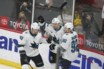 San Jose's Tomas Hertl, center, celebrates with teammates Patrick Marleau, left, and Rudolfs Blacers, right, after Hertl scored a goal during the first period of an NHL hockey game against the Minnesota Wild, Friday, April 16, 2021, in St. Paul, Minn. (AP Photo/Stacy Bengs)