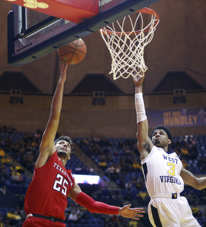 Texas Tech guard Davide Moretti (25) drives to the basket while defended by West Virginia guard James Bolden (3) during the first half of an NCAA college basketball game Wednesday, Jan. 2, 2019, in Morgantown, W.Va. (AP Photo/Raymond Thompson)
