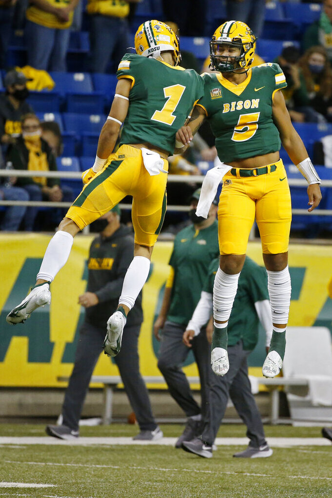 North Dakota State quarterback Trey Lance (5) jumps with wide receiver Christian Watson (1) before the game against Central Arkansas at an NCAA college football game Saturday, Oct. 3, 2020, in Fargo, N.D. (AP Photo/Bruce Kluckhohn)