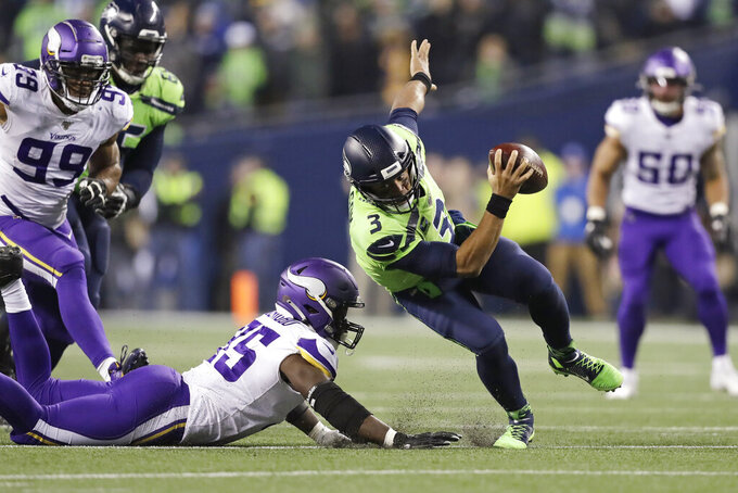 Seattle Seahawks quarterback Russell Wilson (3) scrambles away from Minnesota Vikings' Ifeadi Odenigbo during the second half of an NFL football game, Monday, Dec. 2, 2019, in Seattle. The Seahawks won 37-30. (AP Photo/John Froschauer)