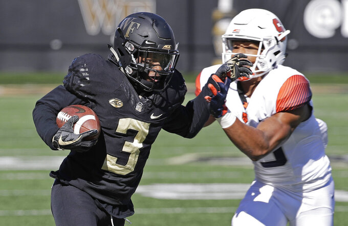 Wake Forest's Greg Dortch (3) runs as Syracuse's Antwan Cordy (8) defends in the first half of an NCAA college football game in Charlotte, N.C., Saturday, Nov. 3, 2018. (AP Photo/Chuck Burton)