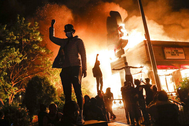 Protestors demonstrate outside of a burning fast food restaurant, Friday, May 29, 2020, in Minneapolis. Protests over the death of George Floyd, a black man who died in police custody Monday, broke out in Minneapolis for a third straight night. (AP Photo/John Minchillo)