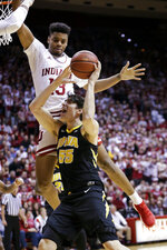 Iowa forward Luka Garza (55) is fouled by Indiana forward Juwan Morgan (13) in the first half of an NCAA college basketball game in Bloomington, Ind., Thursday, Feb. 7, 2019. (AP Photo/AJ Mast)