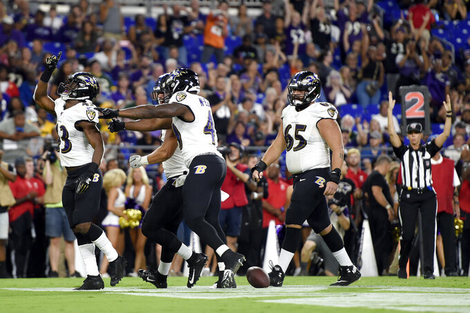 Baltimore Ravens running back Justice Hill, left, reacts with teammates after scoring on a touchdown run against the Green Bay Packers during the second half of an NFL football preseason game, Thursday, Aug. 15, 2019, in Baltimore. (AP Photo/Gail Burton)