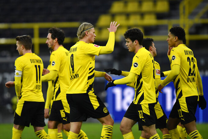 Dortmund's Erling Haaland, right, celebrates with his teammates after Augsburg's Felix Uduokhai scores an own goal during the German Bundesliga soccer match between Borussia Dortmund and FC Augsburg in Dortmund, Germany, Saturday, Jan. 30, 2021. (AP Photo/Martin Meissner, Pool)
