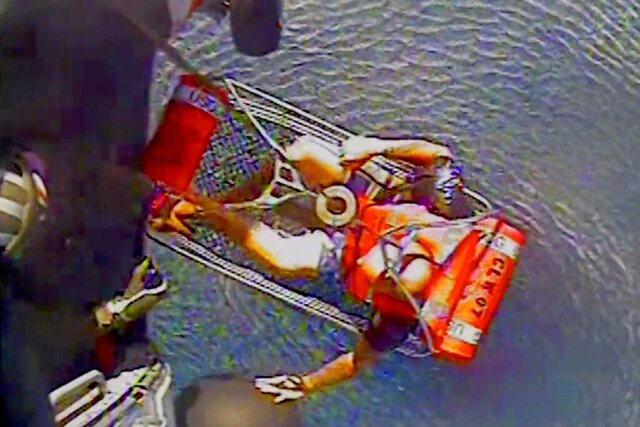 In this July 23, 2020, image made by the U.S. Coast Guard, Coast Guard personnel rescue a commercial fisherman who was clinging to a cooler in the Gulf of Mexico after his boat capsized, days after evacuating a boy and his father from the same vessel, off the coast of St. Petersburg, Fla. A MH-60 Jayhawk helicopter crew dispatched from Air Station Clearwater found Robert Heart, 48, clinging to a cooler in 3 to 4-foot (1-1.2 meter) seas. (U.S. Coast Guard via AP)