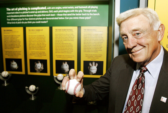 FILE - In this March 29, 2007, file photo, Baseball Hall of Famer Phil Niekro holds a knuckleball at the Great Lakes Science Center in Cleveland. Niekro, who pitched well into his 40s with a knuckleball that baffled big league hitters for more than two decades, mostly with the Atlanta Braves, has died after a long fight with cancer, the team announced Sunday, Dec. 27, 2020. He was 81. (AP Photo/Tony Dejak, File)