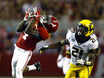 FILE - In this Oct. 13, 2018, file photo, Alabama wide receiver Jerry Jeudy (4) catches a pass next to Missouri defensive back Christian Holmes (21) during the second half of an NCAA college football game, in Tuscaloosa, Ala. Jeudy was named to The Associated Press Midseason All-America team, Tuesday, Oct. 16, 2018. (AP Photo/Butch Dill, File)
