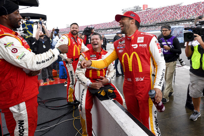 Bubba Wallace, front right, celebrates with crew after a NASCAR Cup series auto race went into a rain delay with him in the lead mid-race Monday, Oct. 4, 2021, in Talladega, Ala. The race was later called called and Wallace announced the winner. (AP Photo/John Amis)
