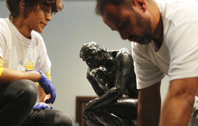 Staff members prepare to move Rodin's The Thinker bronze statue during installation at the Louvre Museum in Abu Dhabi, United Arab Emirates, Sunday, Oct. 27, 2019. The statue created in the 1880s is a one-year loaner from Rodin Museum in France. (AP Photo/Kamran Jebreili)