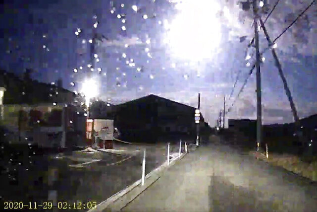 This image made from a drive recorder shows a brightly burning meteor, center top, over a road in Tokushima prefecture, southwestern Japan, Sunday, Nov. 29, 2020. The brightly burning meteor was seen plunging from the sky in wide areas of Japan, capturing attention on television and social media. The meteor glowed strongly as it rapidly descended through the Earth's atmosphere on Sunday. Many people in western Japan reported on social media seeing the rare sight. (Kamio via AP)
