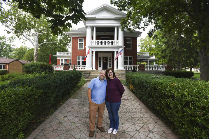 This July 2020 photo shows Kjersten and Greg Offenecker, the owners of a Civil War-era mansion turned bed andbreakfast in St. Johns, Mich.   The owners of the bed and breakfast have removed a Norwegian flag outside of their business after being accused of promoting racism from people who think that it is a Confederate flag.  Kjersten and Greg Offenecker, owners of The Nordic Pineapple, hung the flag opposite of the American flag after they moved into the Civil War-era mansion in 2018. The red flag, with a blue cross superimposed on a white cross, is a nod to Kjersten Offenbecker's grandfather, who was born in Norway.  (Matthew Dae Smith/Lansing State Journal via AP)