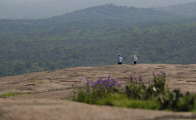 Following social distancing rules and wearing face coverings, visitors hike through Enchanted Rock State Park, Monday, April 20, 2020, in Fredericksburg, Texas. Texas state parks are reopened to the public Monday after they had been closed due to the COVID-19 pandemic, but visitors must follow social distancing rules and wear a facial covering or mask. (AP Photo/Eric Gay)