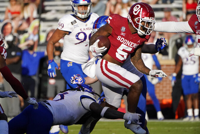 Oklahoma running back T.J. Pledger (5) avoids a tackle by Kansas safety Ricky Thomas, left, in the first half of an NCAA college football game in Norman, Okla., Saturday, Nov. 7, 2020. (AP Photo/Sue Ogrocki)
