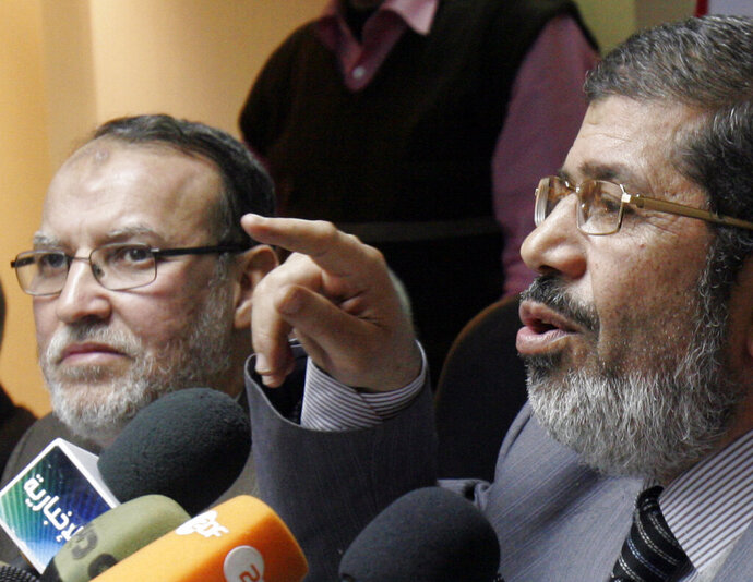 FILE - In this Feb. 9, 2011 file photo, then senior members of Egypt's Muslim Brotherhood Mohamed Morsi, right, and Essam el-Erian hold a press conference in Egypt in Cairo, Egypt. Abdel Moneim Abdel Maqsoud, an Egyptian lawyer said Thursday, Aug. 13, 2020 that el-Erian died of a heart attack in a Cairo prison where he was serving a 25-year sentence. The 66-year-old leader had been behind bars since 2013, following the military overthrow of Egypt's first democratically-elected president, Mohamed Morsi, who had hailed from the Brotherhood's ranks. Morsi also died while in custody. (AP Photo/Mohammed Abou Zaid, File)