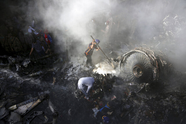 FILE - In this May 22, 2020 file photo, volunteers look for survivors of a Pakistan International Airlines plane that crashed in a residential area of Karachi, Pakistan. Pakistan's government has validated most of the licenses it issued to pilots working abroad, but more than 200 others accused of obtaining tainted licenses were still being investigated, an aviation spokesman said Friday, July 17, 2020, in a move aimed at addressing the concerns of global airlines. (AP Photo/Fareed Khan, File)