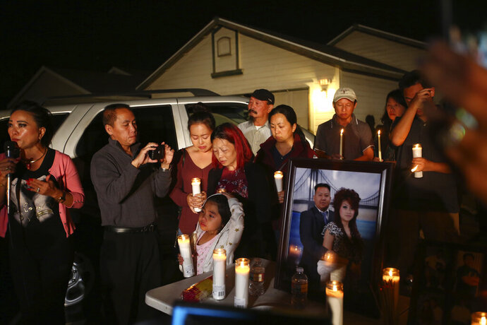 In this photo taken Monday, Nov. 18, 2019, the wife and young daughter of shooting victim Kou Xiong stand among the crowd during the candle light vigil in his honor outside their home in Fresno, Calif. A close-knit Hmong community was in shock after gunmen burst into a California backyard gathering and shot 10 men, killing four.