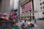 People walk by a souvenir stand in front of the New York Stock Exchange, Friday, July 5, 2019 in New York. (AP Photo/Mark Lennihan)