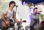 FILE - In this June 25, 2018 file photo, Dan Smyers, left, and Shay Mooney from the band Dan + Shay perform on NBC's
