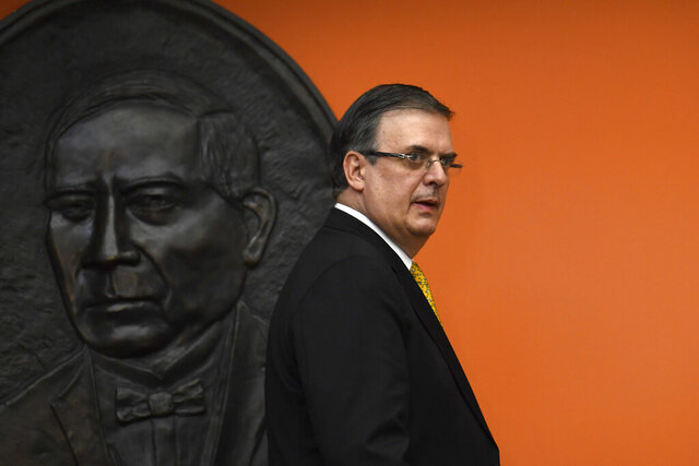FILE - In this Sept. 10, 2019 file photo, Mexican ​Foreign Minister Marcelo Ebrard walks past a plaque of revered former President Benito Juárez as he arrives for a news conference at the Embassy of Mexico in Washington, Tuesday, Sept. 10, 2019. (AP Photo/Susan Walsh, File)